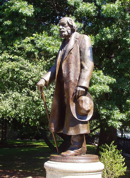 A bronze and marble statue of an elderly Edward Everett Hale stands in a green spacious garden.