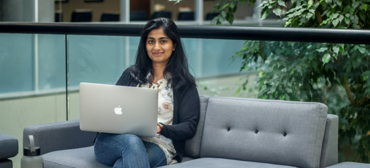 Ashita Kulkarni, a QA Engineer at Carnegie Technologies, completes some of her day's work on her laptop from a sofa in an office atrium.